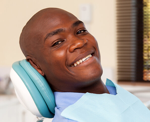 smiling man sitting in a dental chair