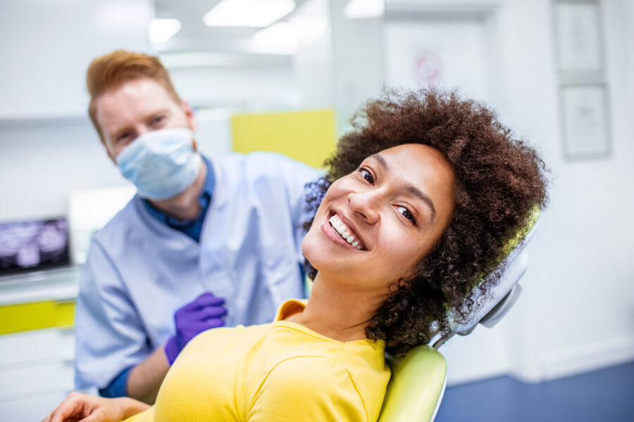 Brunette woman in a yellow shirt smiles while sitting in the dentist chair with a dentist behind her