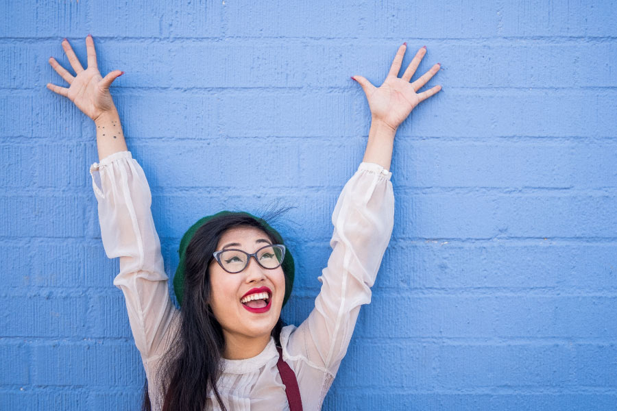 Dark-haired woman with a strong immune system smiles and lifts her arms overhead against a blue wall