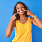 Brunette woman points to her healthy smile while wearing a yellow tanktop against a blue wall