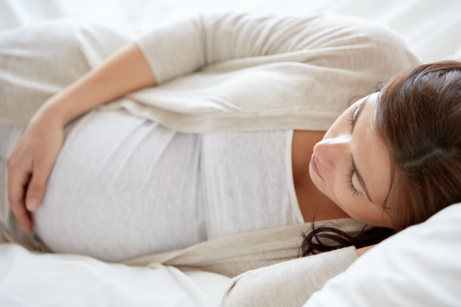 Sidelying pregnant woman touches her belly and thinks about her oral health