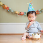 Little boy wears a party hat with a 1 on it to celebrate his first birthday