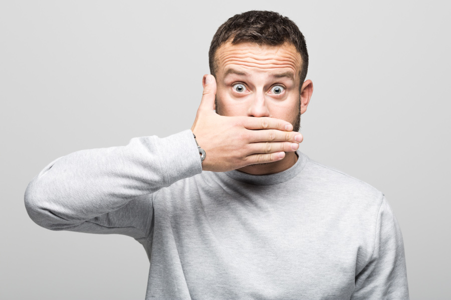 Brunette man in a gray shirt covers his mouth with his hand due to bad breath in Lowell, MA